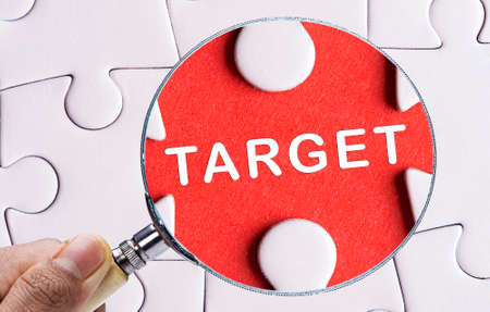 accomplishing: Magnifying glass searching missing puzzle peace TARGET Stock Photo