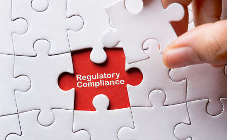 Puzzle with word regulatory and compliance Stock Photo