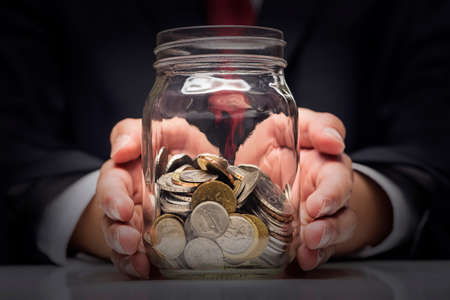 Financial Savings concept - Hand hold coins in clear bottle with vignetting effect