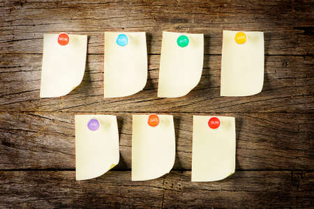 Weekly Sticky Note with colorful pin over wooden background