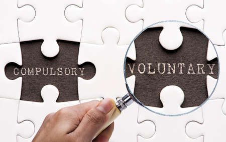 compulsory: Magnifying glass searching missing puzzle peaces Compulsory and Voluntary