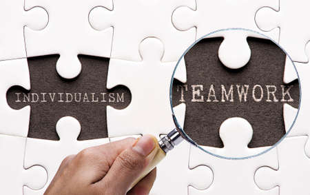 individualism: Magnifying glass searching missing puzzle peaces Individualism and Teamwork Stock Photo