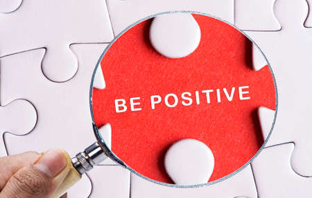 be missing: Magnifying glass searching missing puzzle peace BE POSITIVE Stock Photo