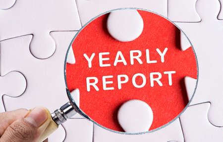 year financial statements: Magnifying glass searching missing puzzle peace YEARLY REPORT