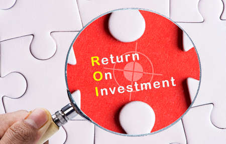 investment concept: Magnifying glass focusing on Return On Investment