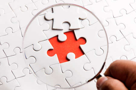 detect: Magnifying glass searching missing puzzle peace Stock Photo