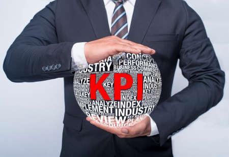 kpi: business executive holding KPI word cloud in a Globe Shape Stock Photo