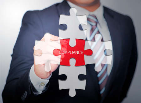 Business Man pointing on jigsaw written word compliance Stock Photo