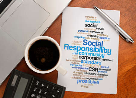 socially: SOCIAL RESPONSIBILITY word cloud arrangement Notebook with text vision on table with coffee, calculator and notebook Stock Photo