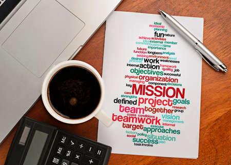 """mision: """"Palabra de la misi�n disposici�n nube"""" Cuaderno con la visi�n de texto en el cuadro con el caf�, calculadora y cuaderno Foto de archivo"""