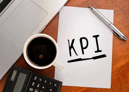 kpi: Notebook with text KPI on table with coffee Stock Photo