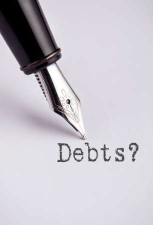 pay off: Debts with pen written on paper