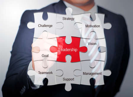 work ethic responsibilities: Business Man pointing on jigsaw written word leadership Stock Photo