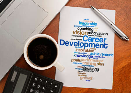 employee development: CAREER DEVELOPMENT word cloud arrangement Notebook with text vision on table with coffee, calculator and notebook