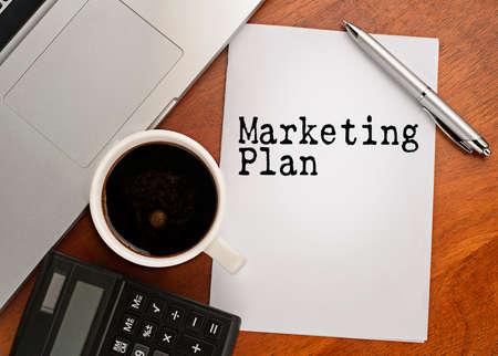 Notebook met tekst marketing plan op tafel met koffie, rekenmachine en notebook