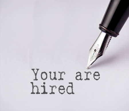 rudimentary: Pen writes you are hired on paper Stock Photo