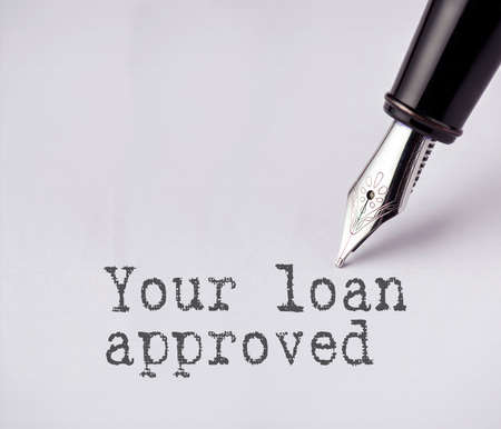homeownership: Pen writes your loan approved on paper