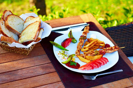 turkish bread: A beatiful Turkish shish kebab plate with nature scene in the background.
