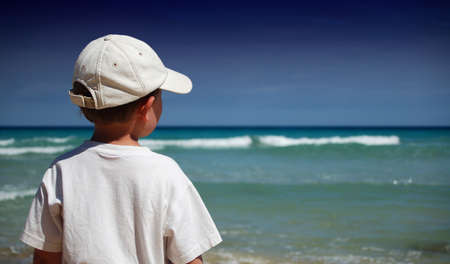 familiy: Boy in white shirt watches the waves on the beach Stock Photo