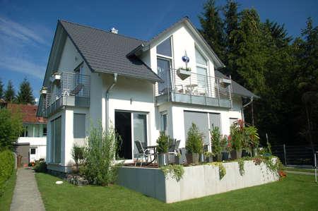 garden city: Casa blanca con verde c�sped y cielo azul