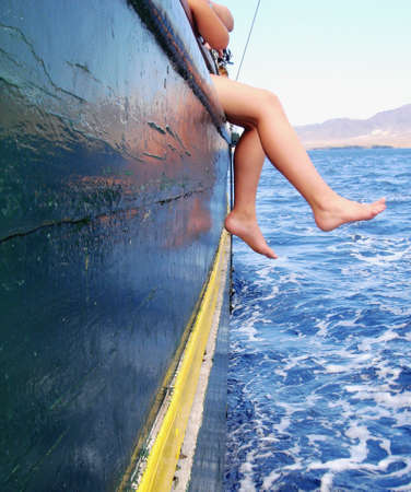 boy sitting on the ship´s rail with his legs above the ocean Stock Photo