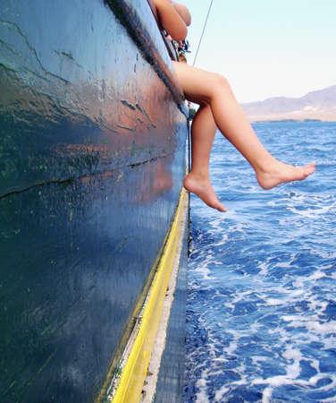 Junge sitzt auf dem Schiff im Eisenbahnnetz mit seinen Beinen über dem Ozean  Standard-Bild - 765101