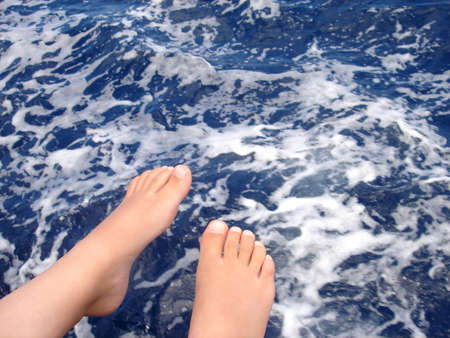 boy sitting on a boat with his feet above the ocean