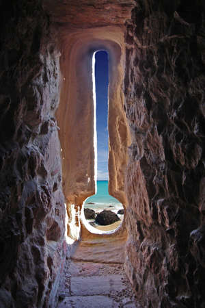 View through an arrow slit of an ancient castle to a sunny beach with rocks