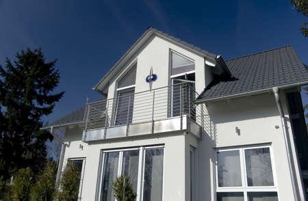 Weißes Haus mit Balkon an einem sonnigen Tag mit blauem Himmel Standard-Bild - 837961