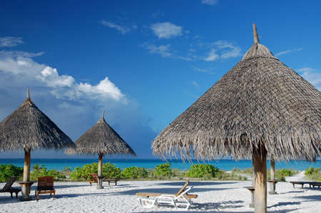 tropical beach on the maldives with canvas chairs and sunshades Standard-Bild