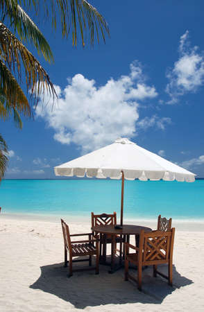 dining place with wooden chairs, table and white sun shade in a cafe on an maldivan island in the Indian Ocean photo