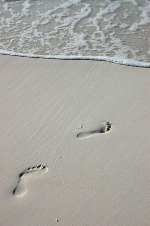 footprints in the sand on a white maldivian beach