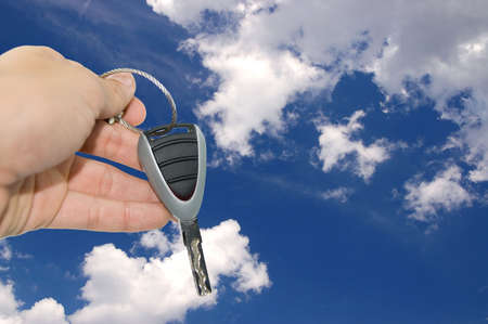 hand with car key in front of blue sky Stock Photo