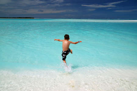 Boy jumps into the turquoise water on a tropical beach              版權商用圖片