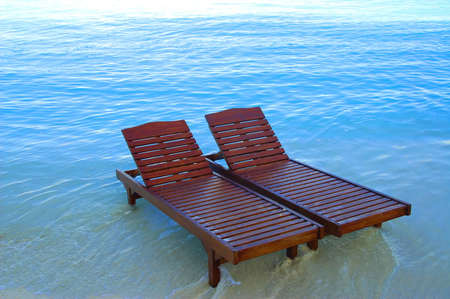 canvas chairs in the sea on a tropical beach
