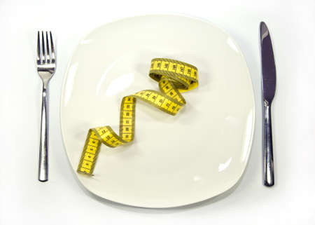 measuring tape on a dish. Symbol of dieting photo