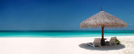Plážová lehátka a deštník na krásném ostrově, panoramatický výhled s hodně copyspace