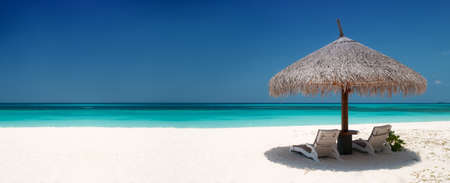 strandstoel: Strandstoelen en parasol op een prachtig eiland, panoramisch uitzicht met veel copyspace Stockfoto