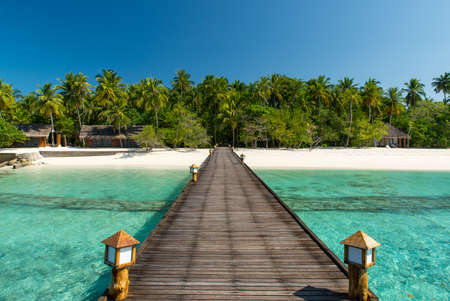 footbridge over turquoise ocean on an maldivian island 免版税图像