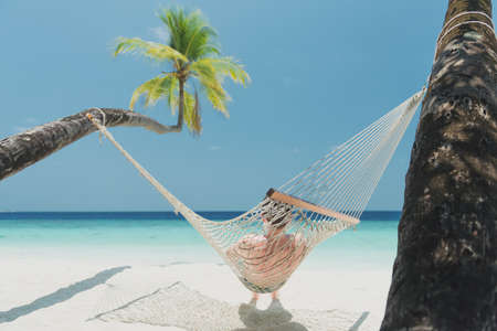 teen boy in beach hammock on the maldives