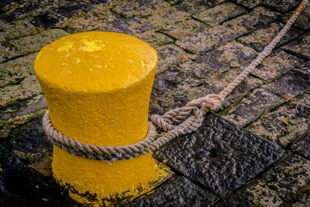 fixed line: Yellow bollard at the old harbor of dunbar, scottland Stock Photo