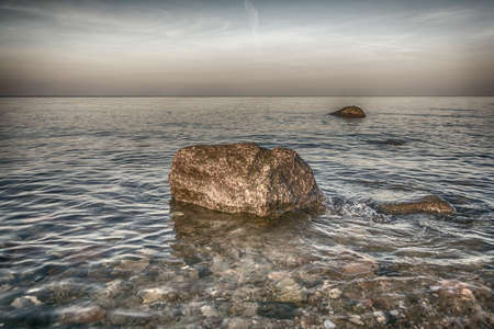 Baltic sea coast at frozen golden romantic sunset time stones, beach, Natural background. Stock Photo