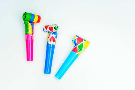 favor: Multicolor party blowers on white background and confetti