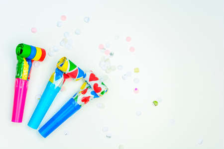 Multicolor party blowers on white background and confetti