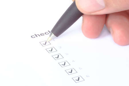 Businessman checking mark on checklist with marker over white