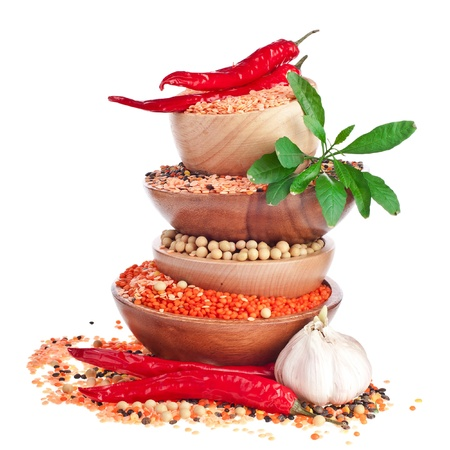 köri: Different colorful lentils in a wooden bowl, soya beans, red chilli peppers with leaves and garlic  Stok Fotoğraf