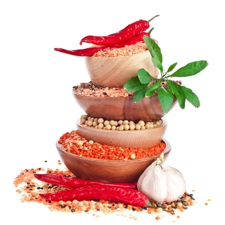 indian spices: Verschillende kleurrijke linzen in een houten kom, sojabonen, rode pepers met bladeren en knoflook