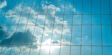 sky reflection: Reflection of a cloudy sky in glass wall of an office building Image ID: 12995866