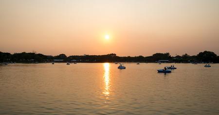 fibra de vidrio: relajarse en el barco del pedal en la noche con la puesta del sol y el cielo crepuscular