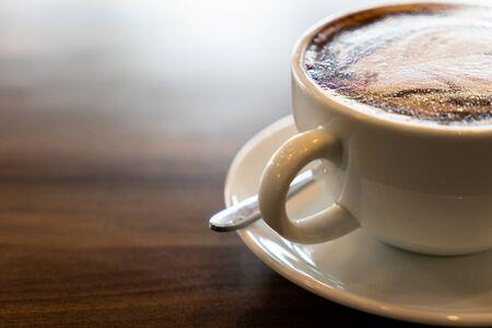 Hot coffee cappuccino latte spiral foam on dark wooden background Banco de Imagens